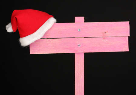 Wooden road sign with Santa hat black background photo
