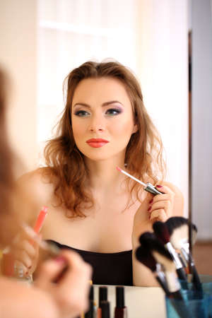 Young beautiful woman making make-up near mirror Stock Photo - 17545196