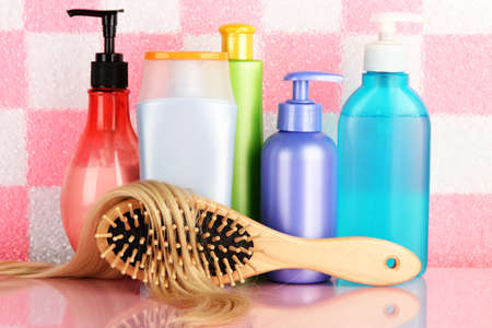 comb brush with hair and cosmetic bottles in bathroom Stock Photo - 17263875