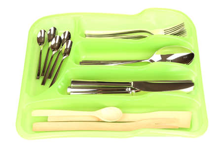 Green plastic cutlery tray with checked silver cutlery and wooden spoons isolated on white photo