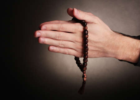 Hands holding wooden rosary on grey background photo