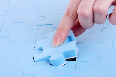 Hand collecting a part of a puzzle Stock Photo - 17292163