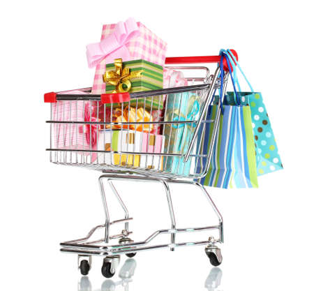 shopping cart with bright gifts and paper bags isolated on white  photo