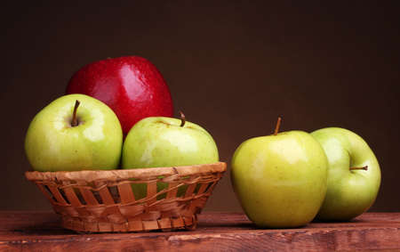 juicy sweet apples in basket on wooden table on brown background Stock Photo - 17291836