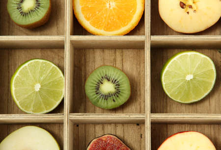 Sliced fruits in wooden box background photo