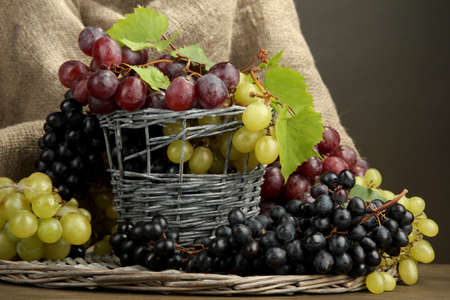assortment of ripe sweet grapes in basket, on grey background photo