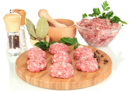 Raw meatballs with spices isolated on white photo