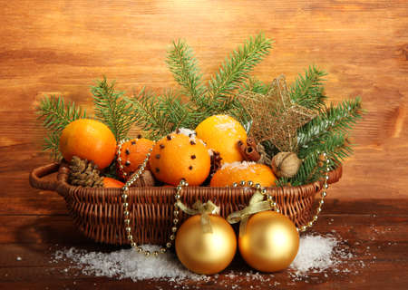 christmas composition in basket with oranges and fir tree, on wooden background Stock Photo - 17292650