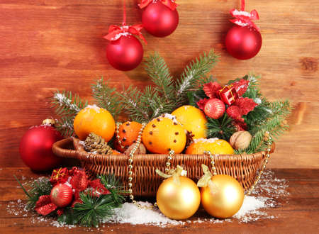 christmas composition in basket with oranges and fir tree, on wooden background photo
