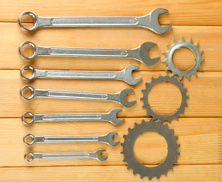 Metal cogwheels and spanners on wooden background Stock Photo - 17292161