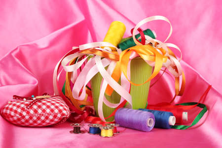 Color bucket with multicolor ribbons and thread on pink fabric background photo