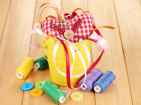 Color bucket with multicolor ribbons and thread on wooden background Stock Photo - 17291989