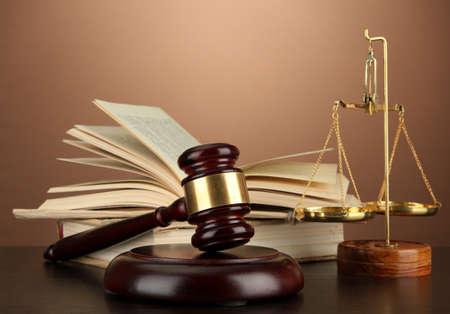 justiz: Goldene Waage der Gerechtigkeit, Hammer und B�cher auf braunem Hintergrund