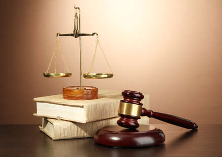 justice: Golden scales of justice, gavel and books on brown background Stock Photo