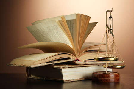 Gold scales of justice and books on brown background photo
