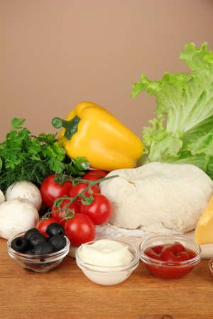 Ingredients for pizza on wooden table on brown background photo