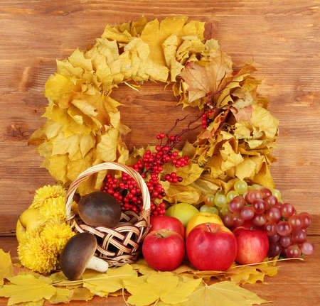Autumnal composition with yellow leaves, apples and mushrooms on wooden background photo
