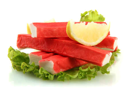 Crab sticks on lettuce leaves with lemon, isolated on white photo