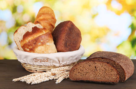 Fresh bread in basket on wooden table on natural background Stock Photo - 17292544