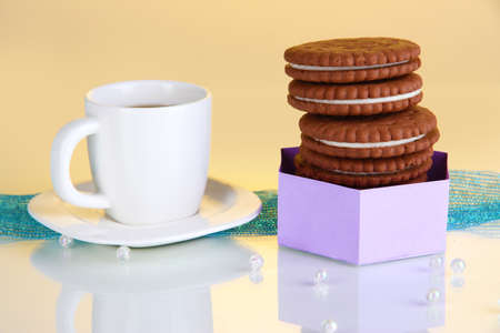 Chocolate cookies with creamy layer and cup of coffe on yellow background photo