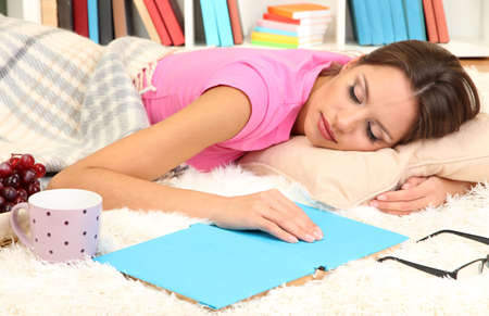 Young female asleep while reading book on floor Stock Photo - 17544436