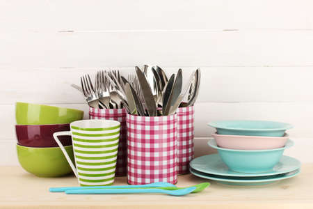 Cups, bowls nd other utensils in metal containers isolated on light background photo