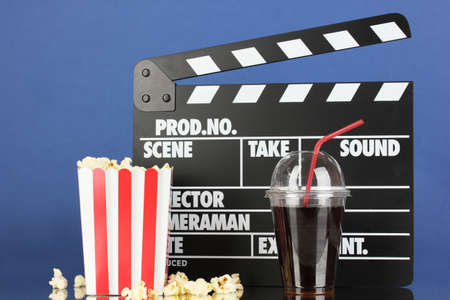 Movie clapperboard, cola and popcorn on blue background Stock Photo - 17292069