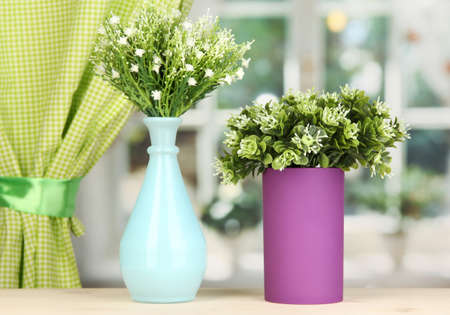 Decorative flowers in vases on windowsill photo