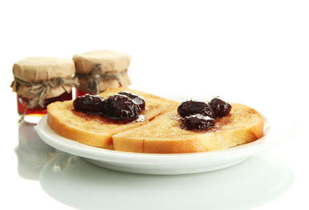 White bread toast with jam on plate, isolated on white photo
