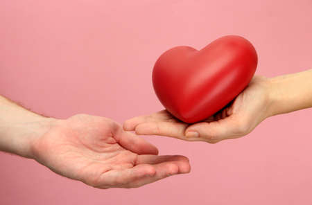 Red heart in woman and man hands, on pink background Stock Photo - 17291849