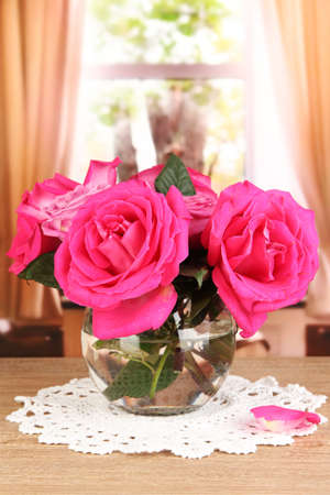 Beautiful pink roses in vase on wooden table on window background Stock Photo - 17292022