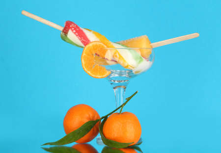 Two fruit juice ice in vase on blue background photo