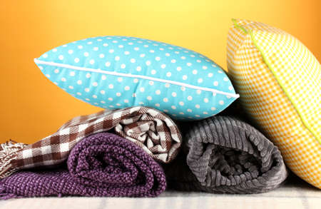 Plaids and color pillows on yellow background photo