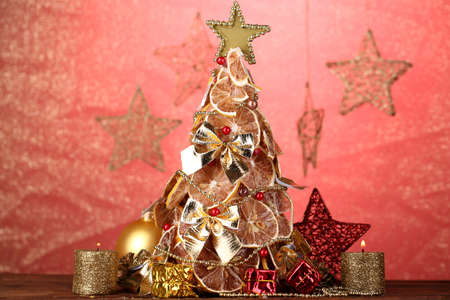 beautiful christmas tree of dry lemons with decor, on red background photo