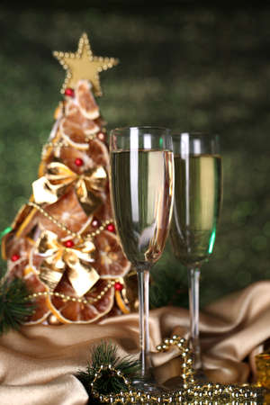 beautiful christmas tree and  glasses of champagne on  shine green background photo