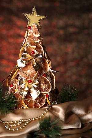 beautiful christmas tree of dry lemons with decor, on  shine red background photo
