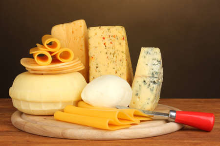 Various types of cheese on wooden table on brown background Stock Photo - 17291952