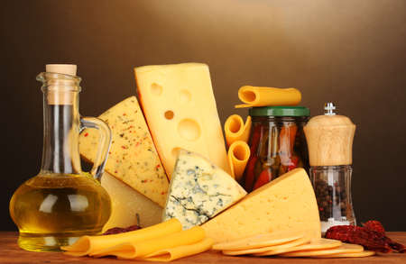 Various types of cheese on wooden table on brown background photo