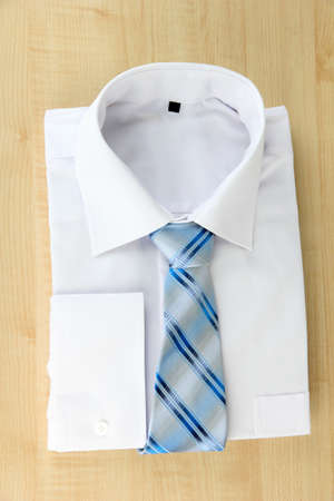 New white mans shirt with color tie on wooden background photo