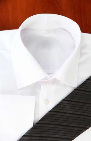 New white man's shirt with color tie on wooden background photo