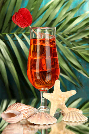 Alcoholic fruit cocktail with ice on tropical background photo