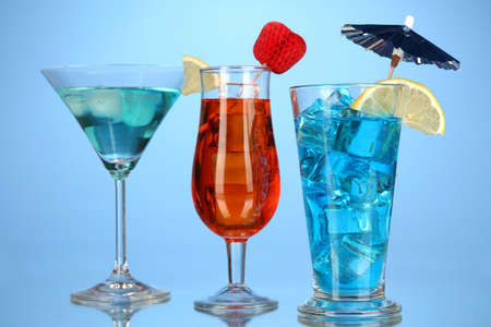 Alcoholic cocktails with ice on blue background photo