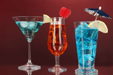 Alcoholic cocktails with ice on darck red background photo