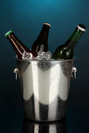 Beer bottles in ice bucket on darck blue background photo