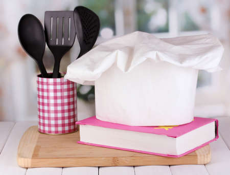 Chef's hat with spoons and cook book on board on wooden table on window background Imagens