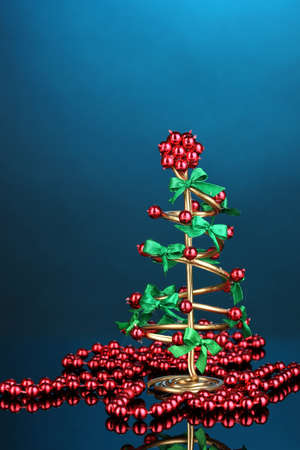 Wire Christmas tree with beads on blue background photo