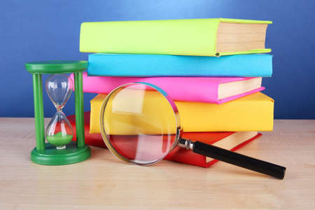color books with magnifying glass on table on blue background photo