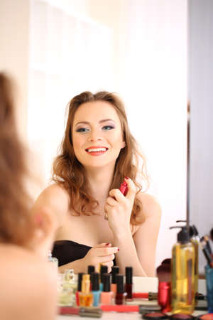 Portrait of attractive woman applying parfume photo