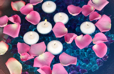 Rose petals and candles in water close-up photo