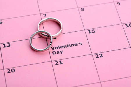 Notes on the calendar (valentines day) and wedding rings, close-up photo
